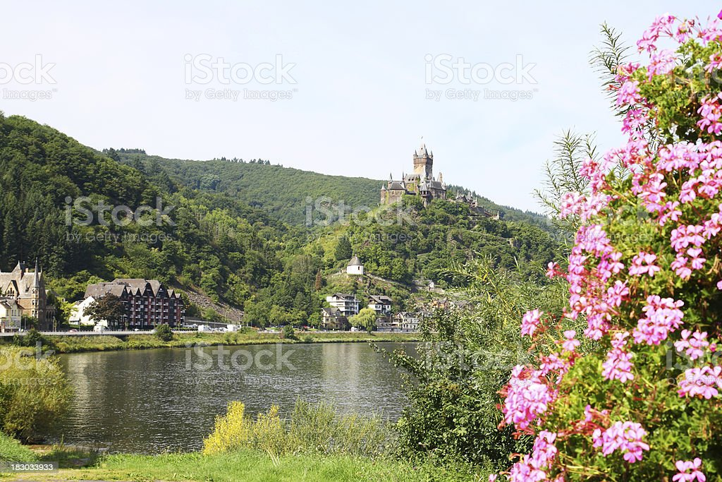 Reichsburg castle in Cochem behind river Mosel and flower arrangement royalty-free stock photo