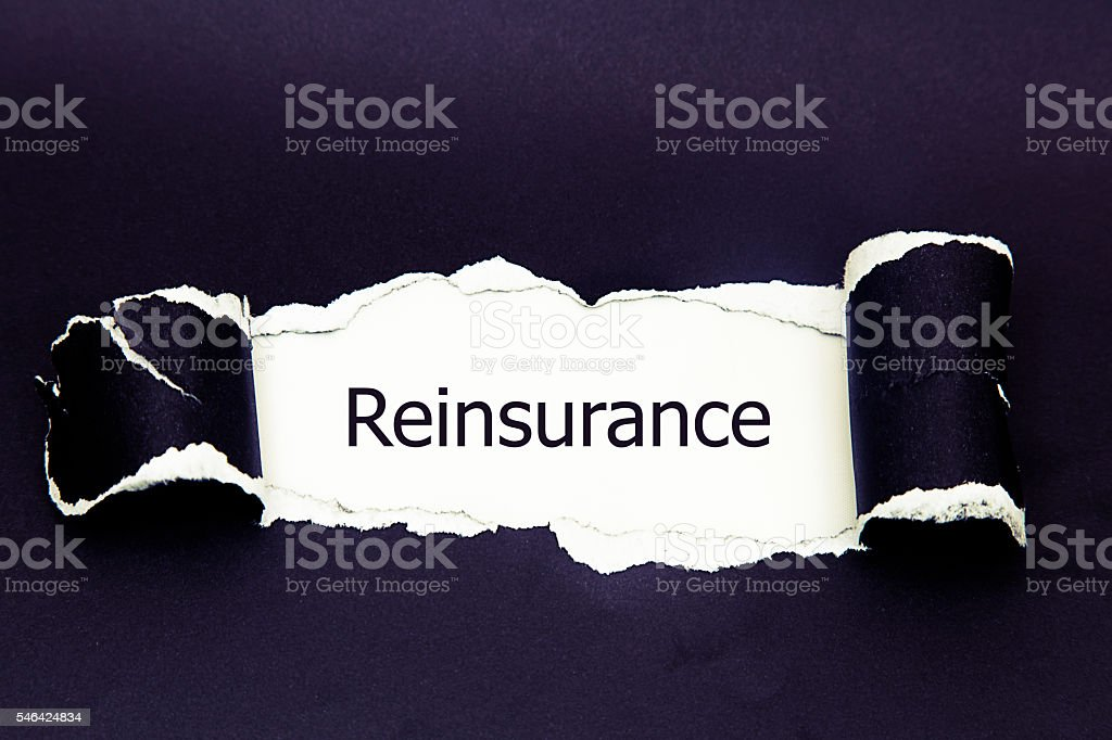 Reinsurance word written under torn paper. stock photo