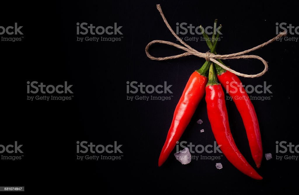 Related hot red chili peppers and a large crystal salt stock photo