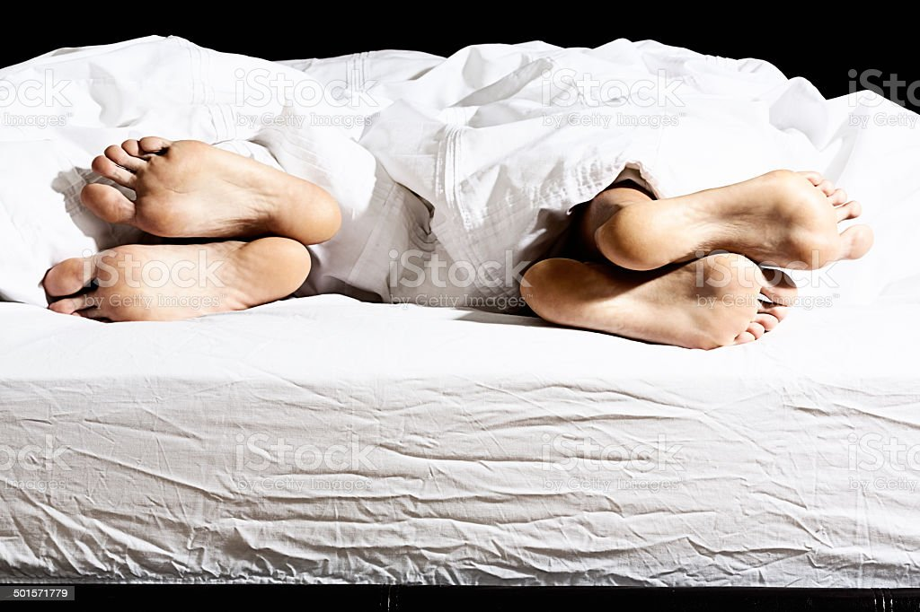 Relationship difficulties. Feet in bed turn away from each other stock photo