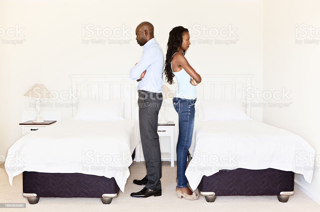 Relationship issues: unhappy couple backs to each other in bedroom royalty-free stock photo