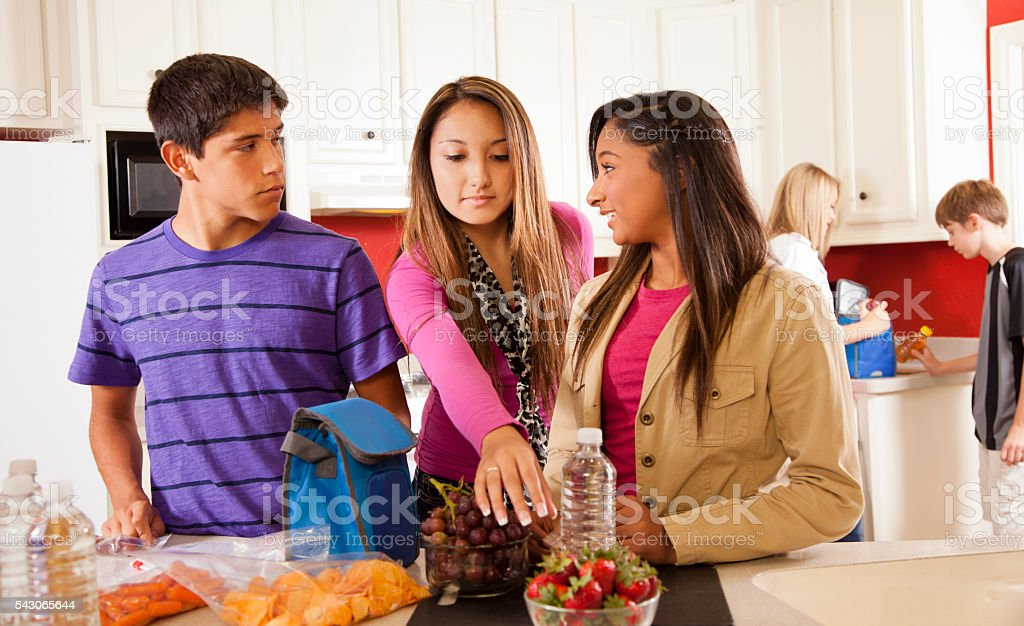Relationships: Foster home teens in kitchen making lunches. stock photo
