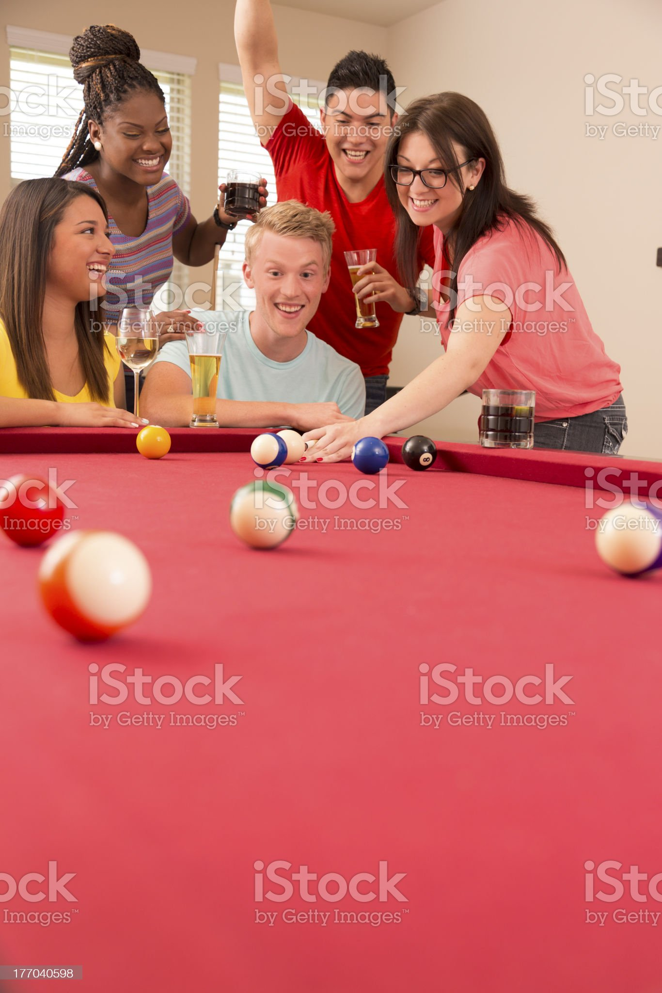 Relationships:  Friends enjoying a round of pool in gameroom. royalty-free stock photo