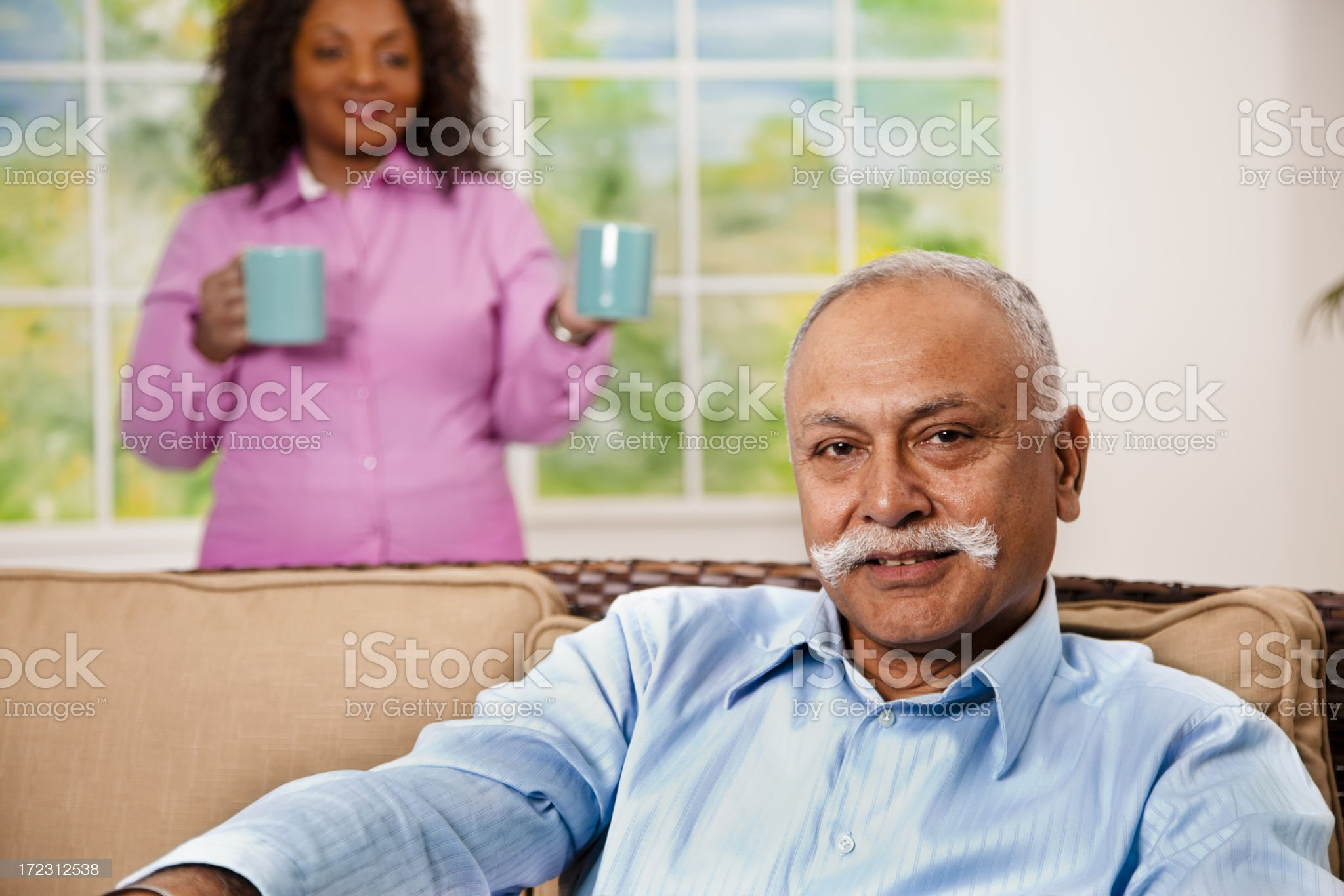 Relationships:  Mid-adult woman brings coffee to senior friend on couch royalty-free stock photo