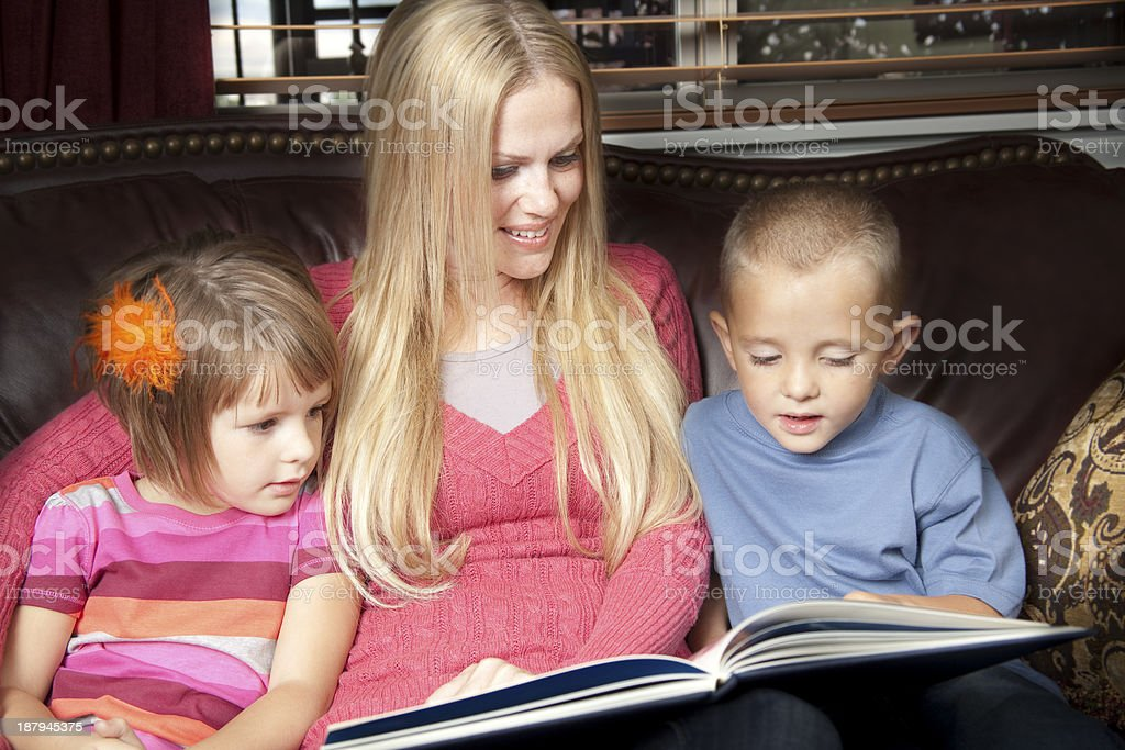 Relationships:  Mother reads to her children. stock photo