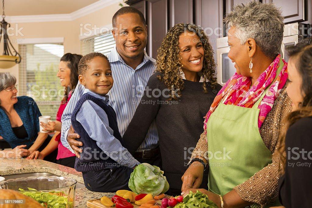 Relationships: Multi-generation family prepares dinner in kitchen. stock photo