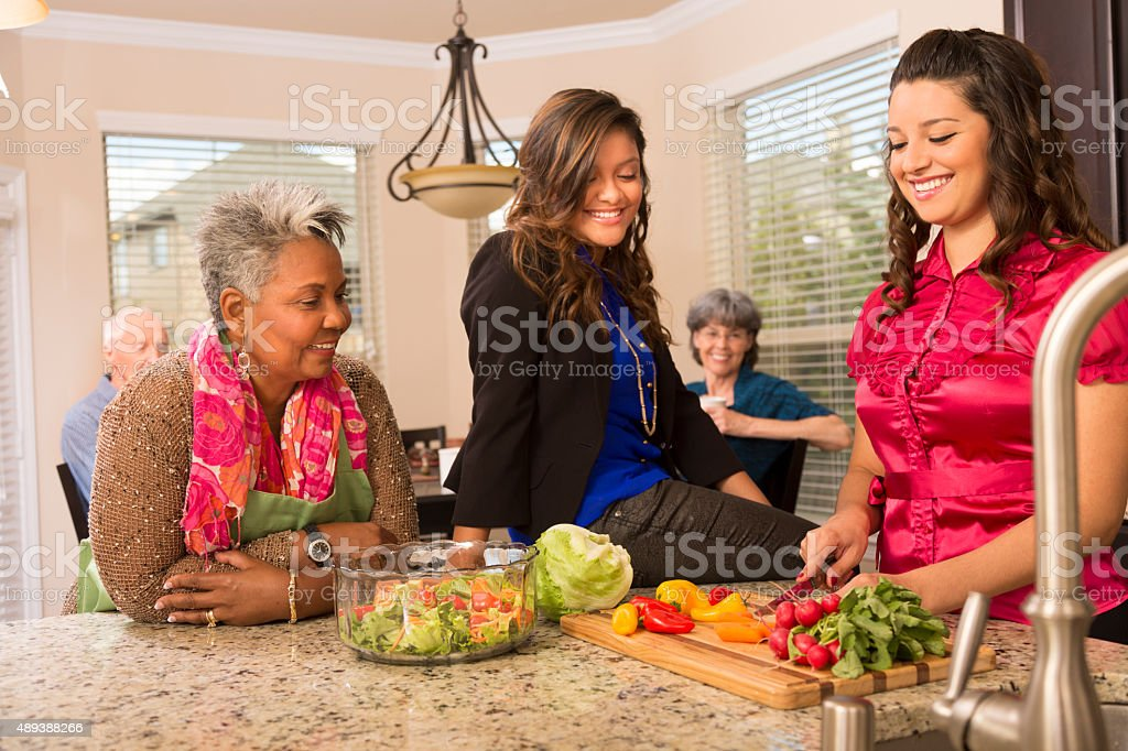 Relationships: Senior woman, family and friends cook in home kitchen. stock photo