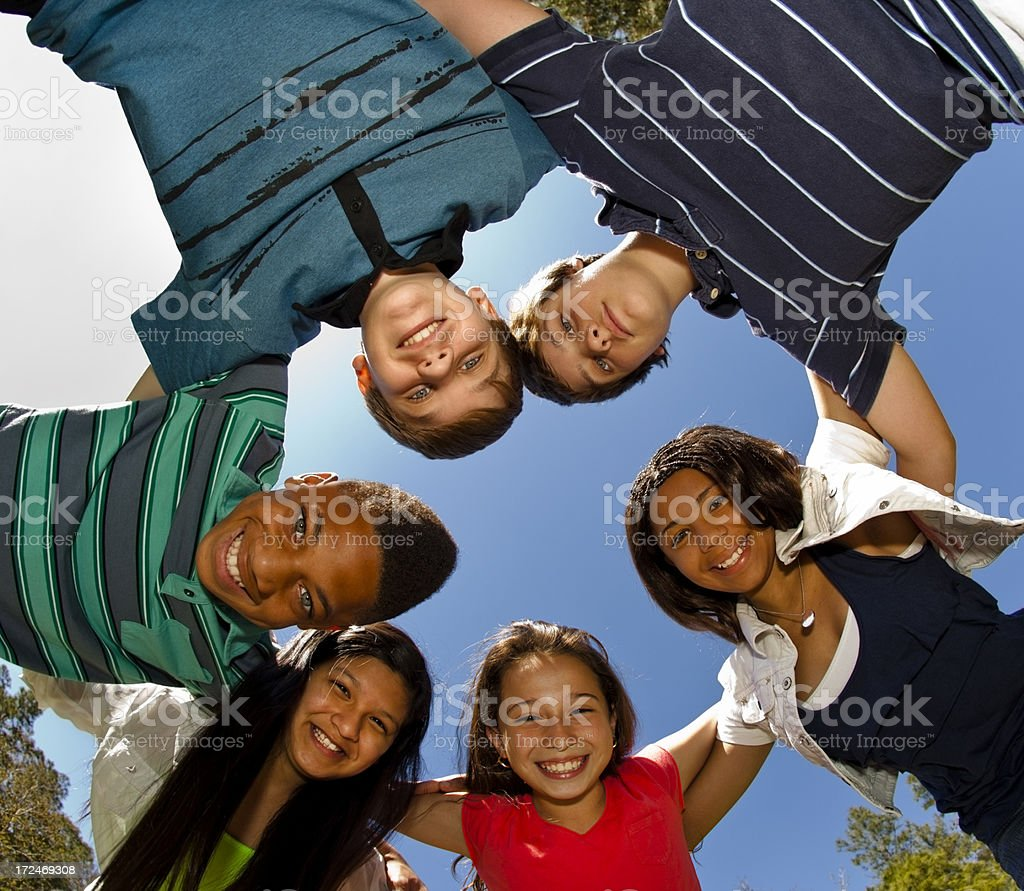 Relationships: Teenagers Smiling in a huddle against clear blue sky royalty-free stock photo