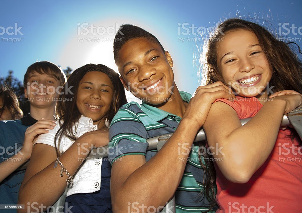 Relationships: Teenagers smiling in a row against clear blue sky stock photo