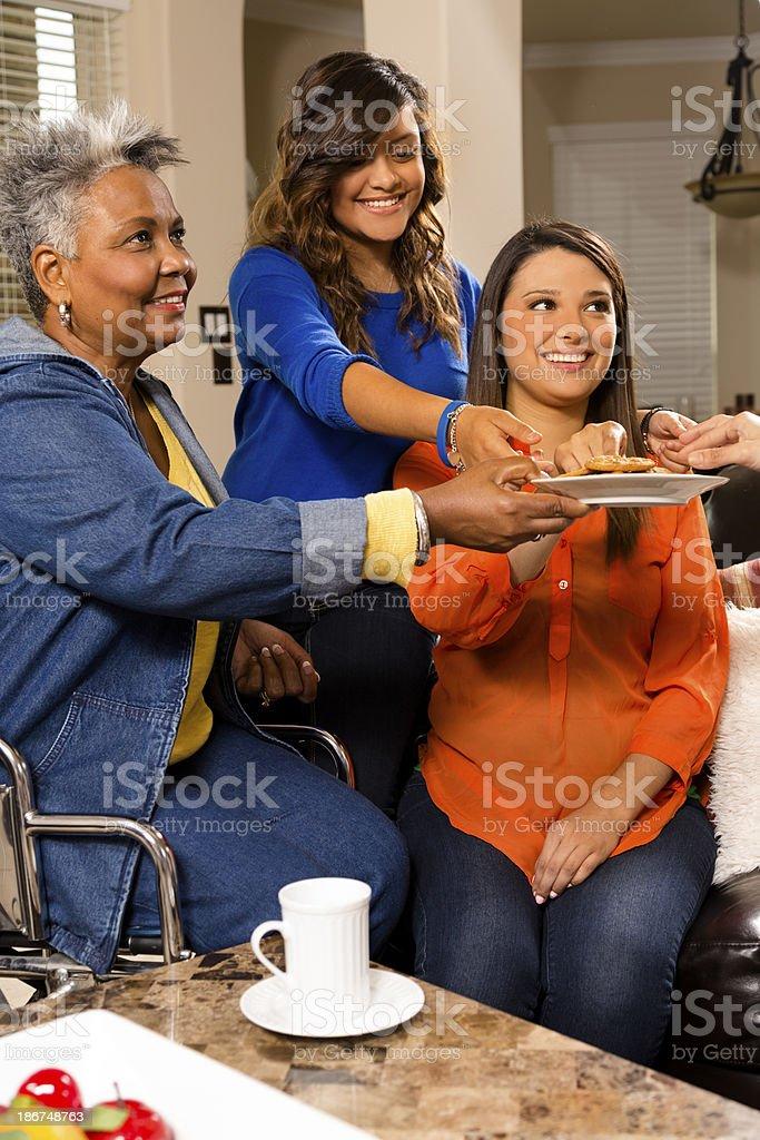 Relationships, Volunteers: Grandmother, grandchildren share cookies in home. stock photo