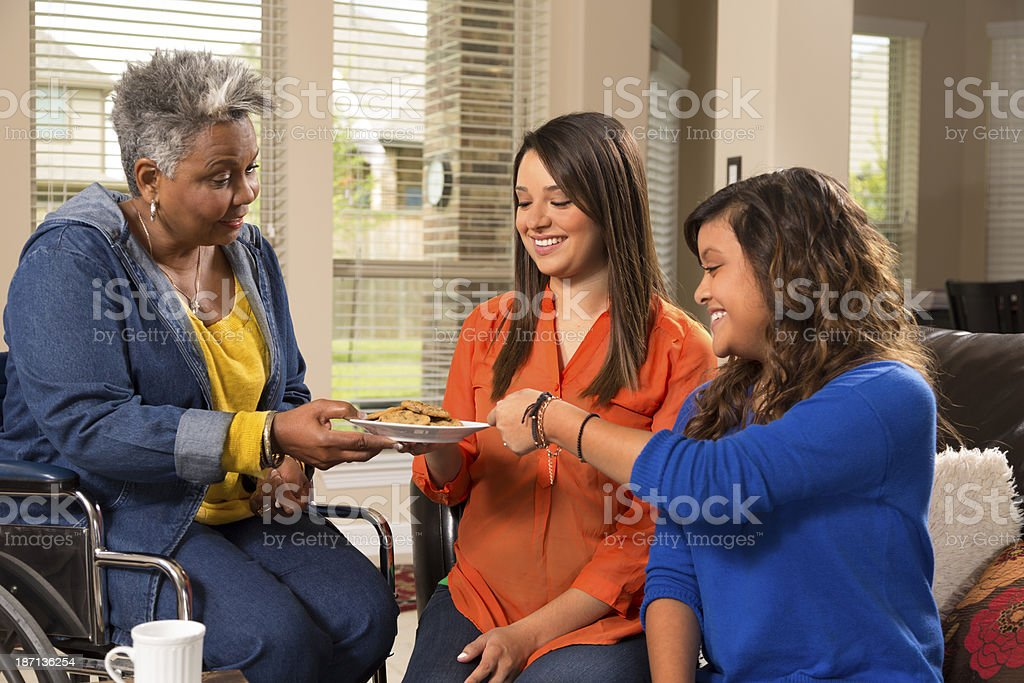 Relationships, Volunteers: Grandmother, grandchildren share cookies in home. stock photo