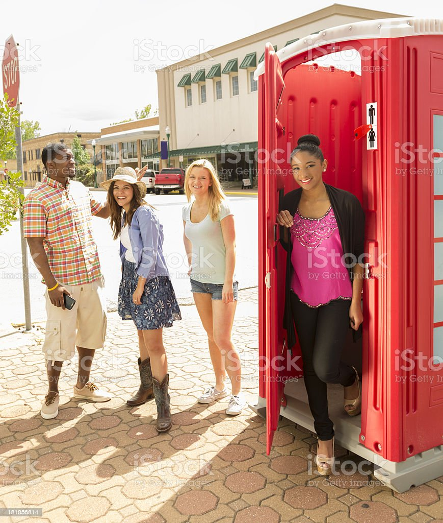 Relationships:  Young adults outside toilet fashioned like English phone booth stock photo