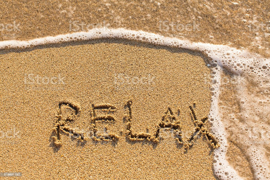 Relax - drawn on the sand of a sea beach. stock photo