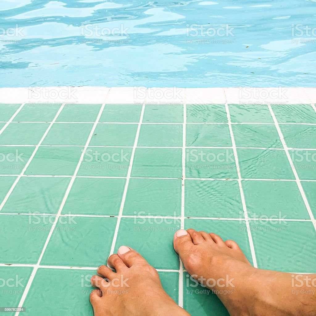 Relax time on swimming pool, feet in the water royalty-free stock photo