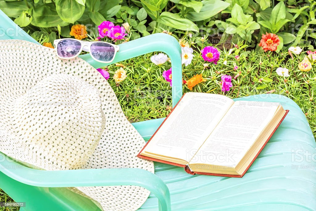 Relax with a book in a flowering summer garden stock photo