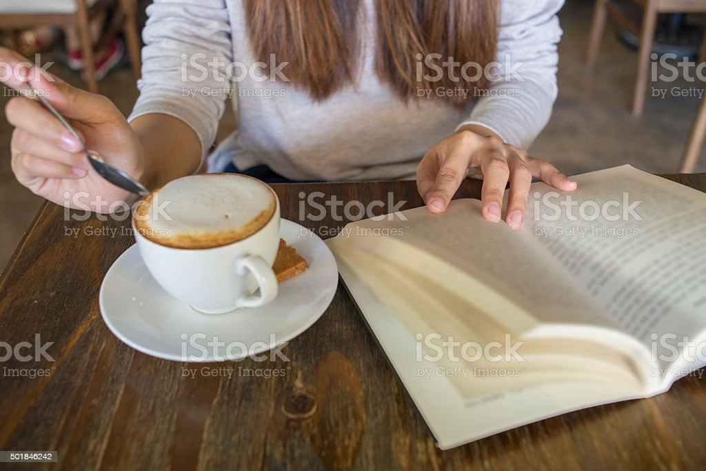 Relax with a cup of cappuccino and favorite book stock photo