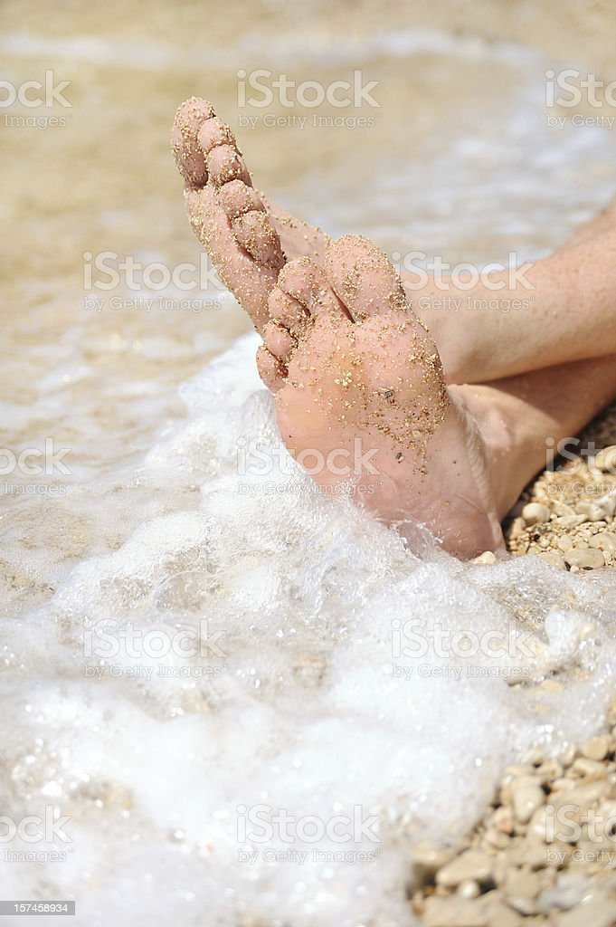 Relaxation on beach, detail of male feet royalty-free stock photo