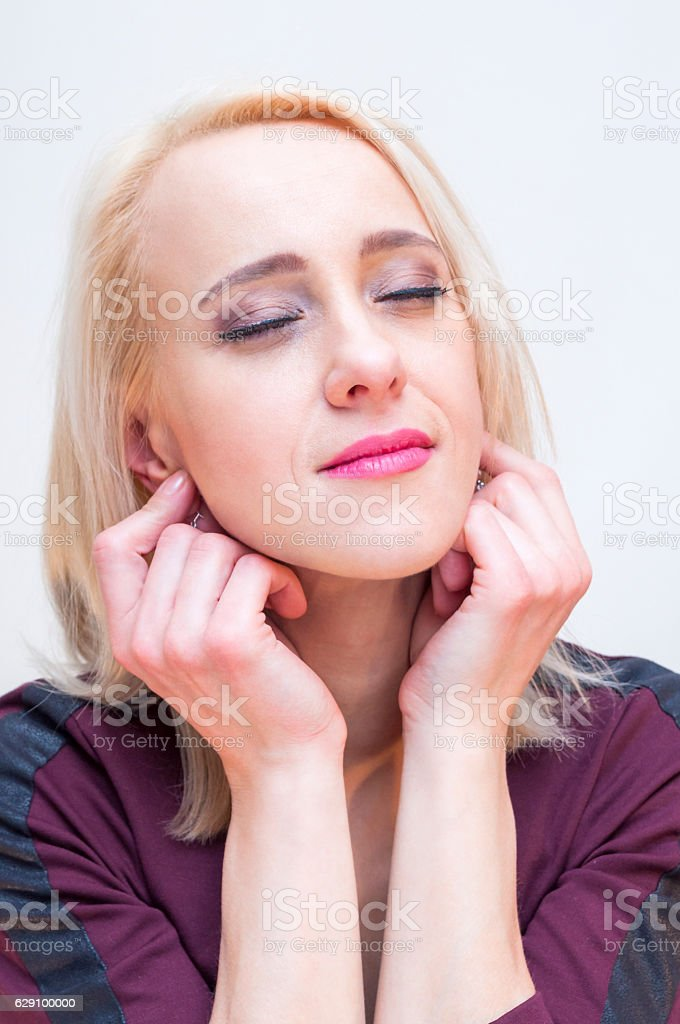 Relaxation techniques. Young blonde woman holding earlobes with eyes closed. stock photo