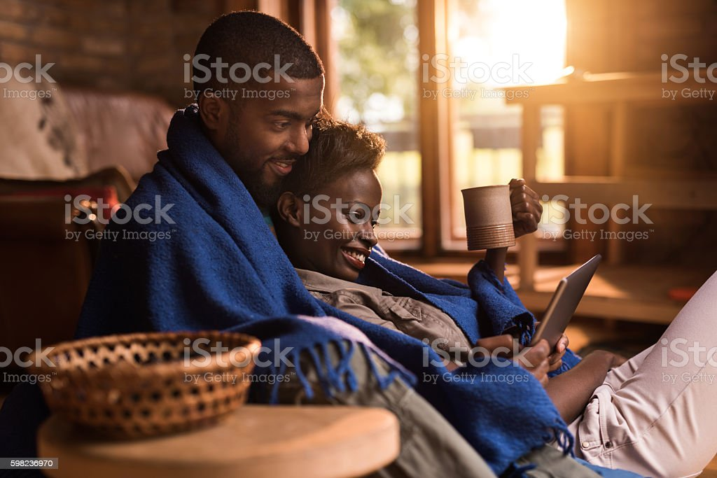 Relaxed African American couple using digital tablet at home. stock photo