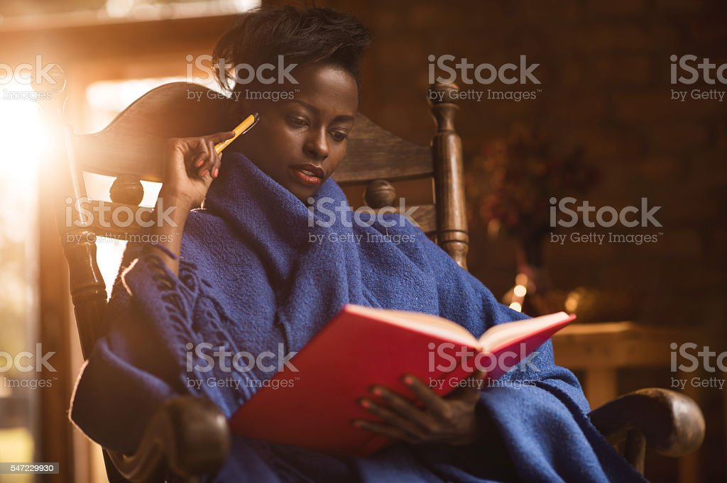 Relaxed African American woman reading a book at home. stock photo