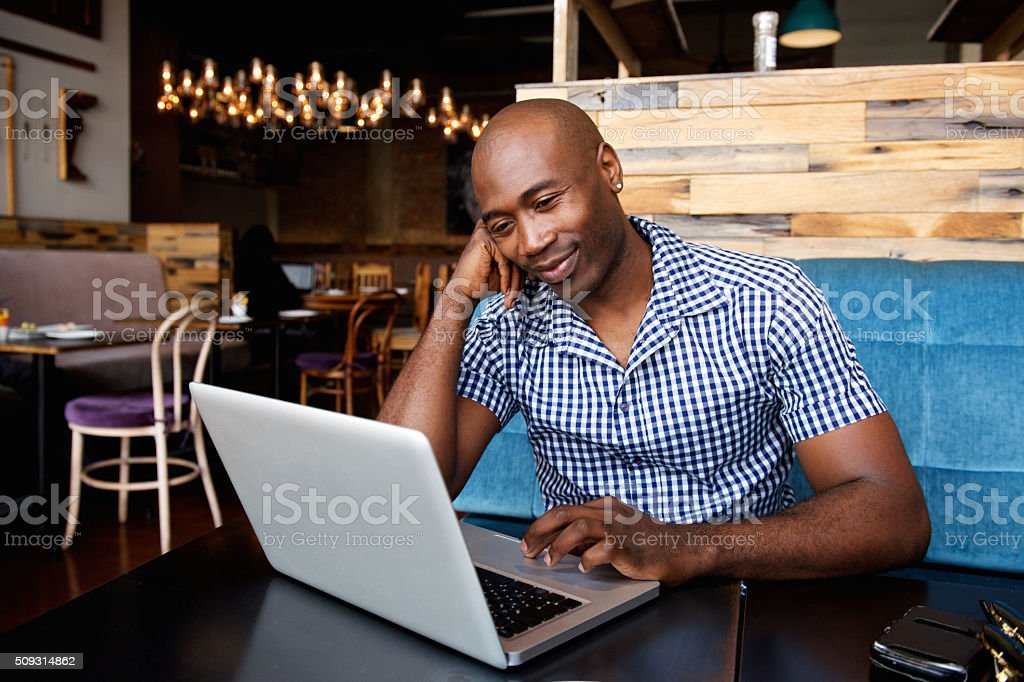 Relaxed african man at a cafe table using laptop stock photo