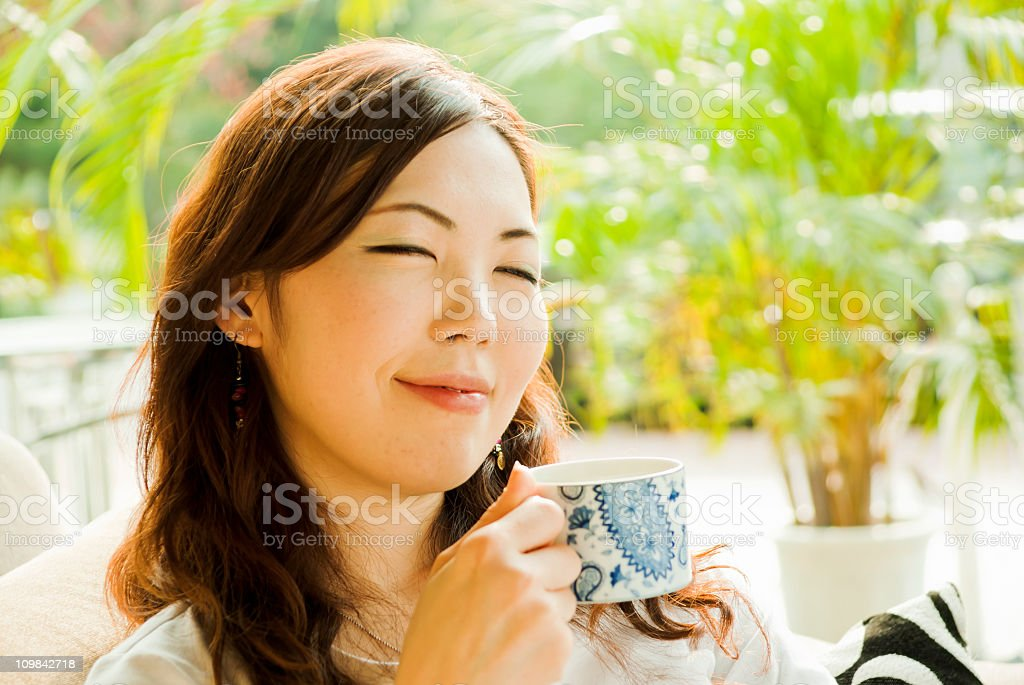 Relaxed Asian woman having coffee at a cafe stock photo