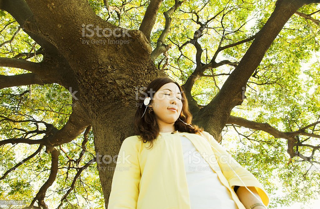 Relaxed Asian woman, listening to music under a tree stock photo