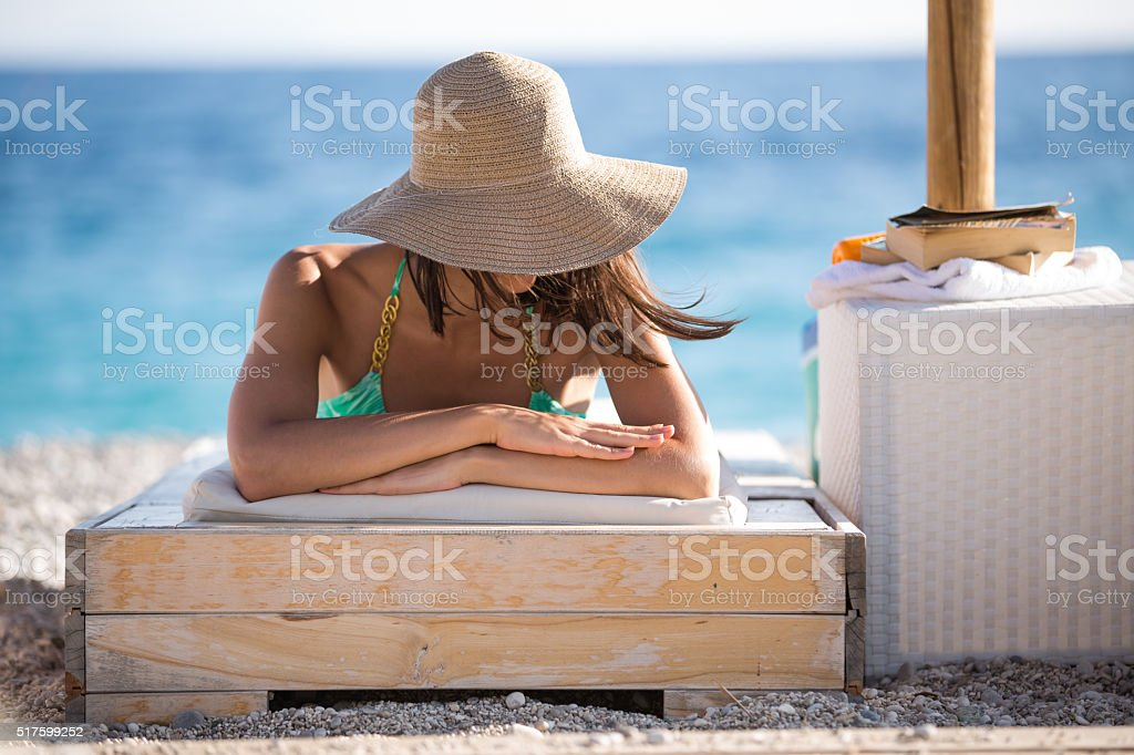 Relaxed beach woman enjoying summer,sunbathing on sun lounger.SPF protection stock photo