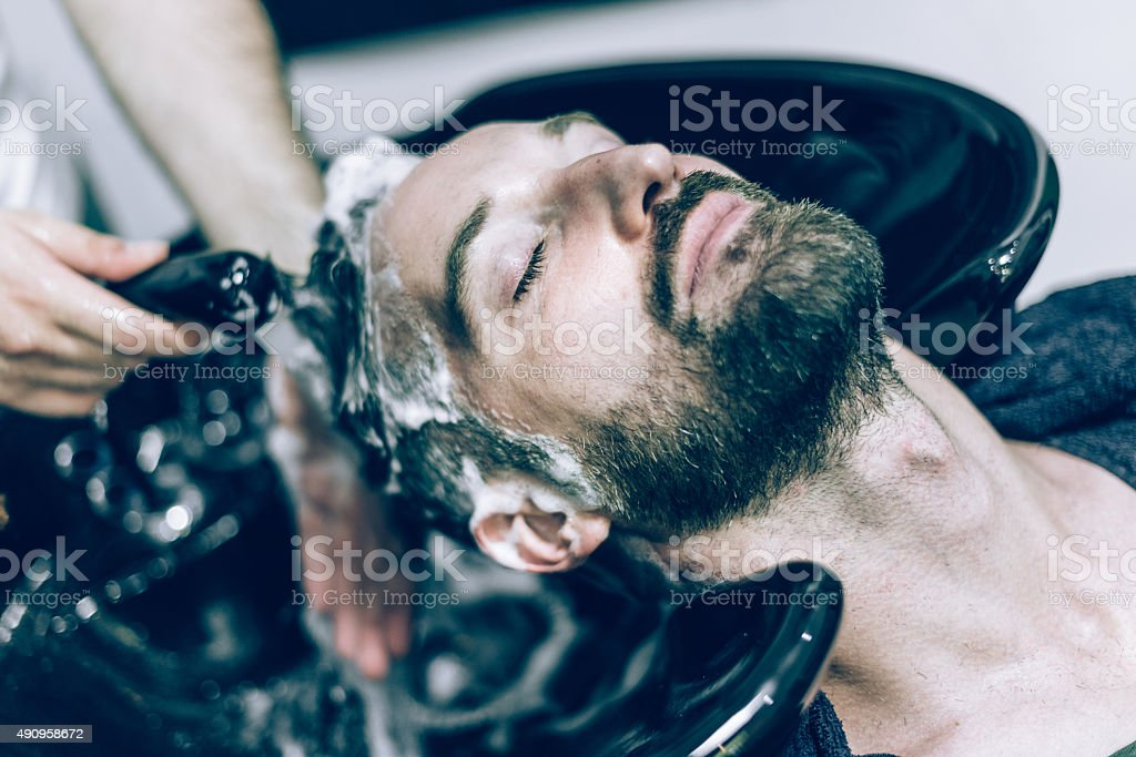 relaxed bearded man receives hair shower stock photo