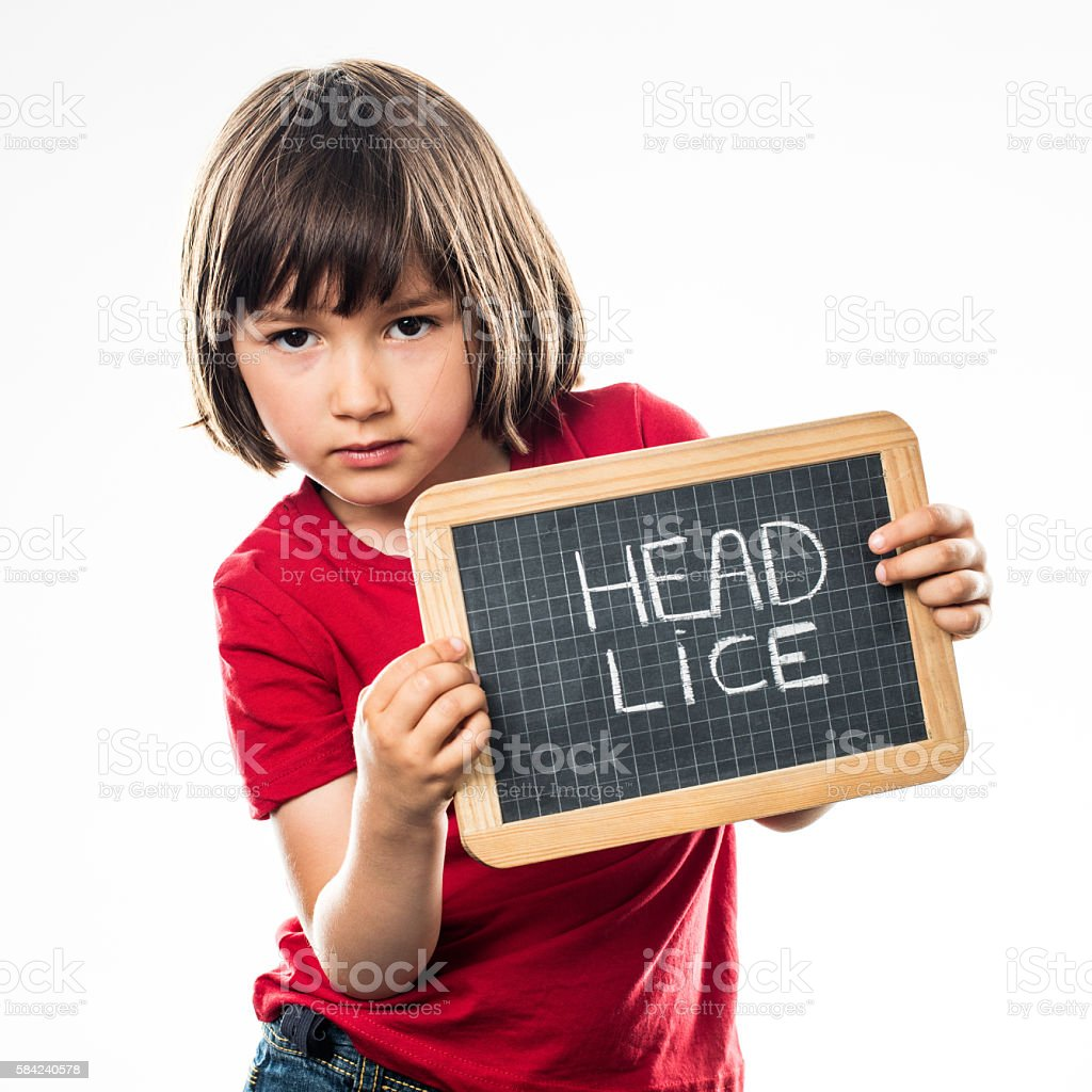 relaxed beautiful little child with school slate against head lice stock photo