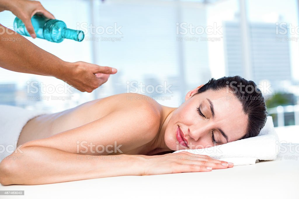 Relaxed brunette receiving back massage stock photo