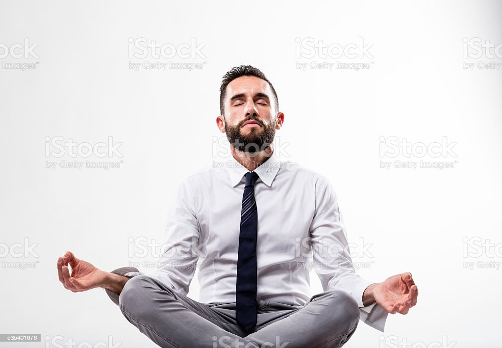 relaxed business man in meditation pose stock photo