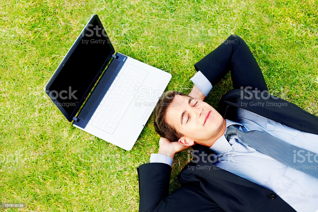 Relaxed business man lying on field with laptop royalty-free stock photo