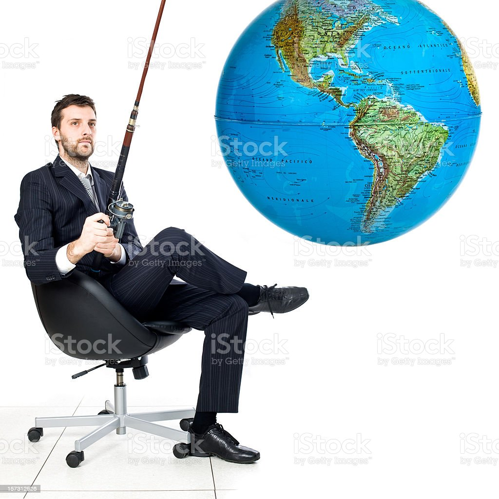 relaxed business man owns the world with fishing rod royalty-free stock photo