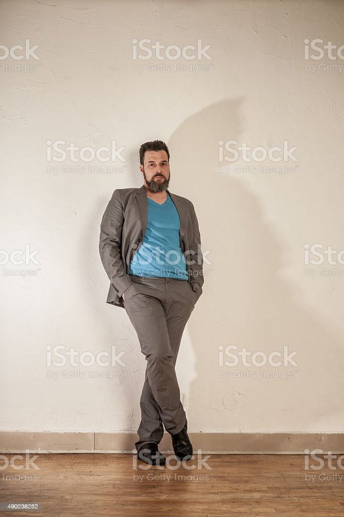 Relaxed business man with beard leaning on wall stock photo
