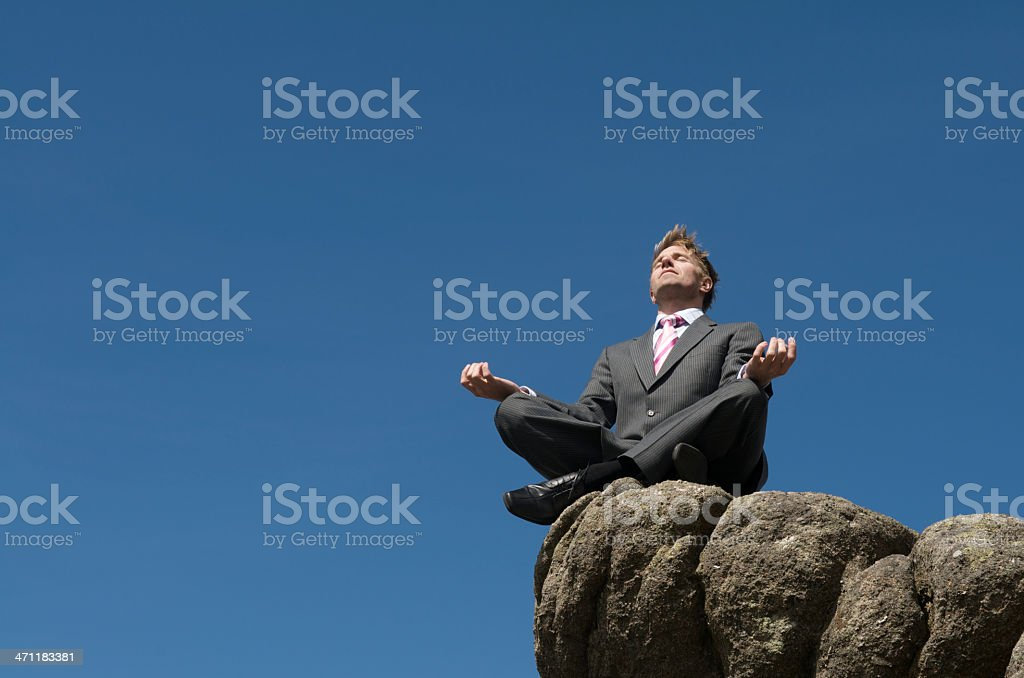 Relaxed Businessman Doing Yoga on Blue Sky Rock royalty-free stock photo