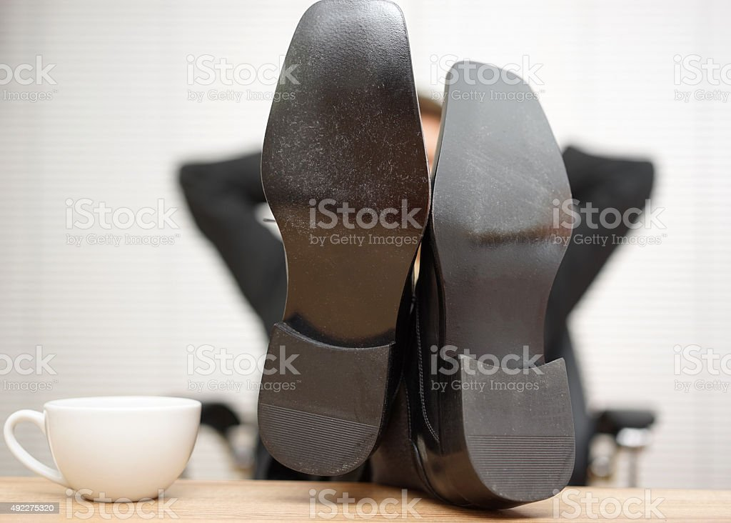 Relaxed businessman is sitting  with feet on the desk stock photo