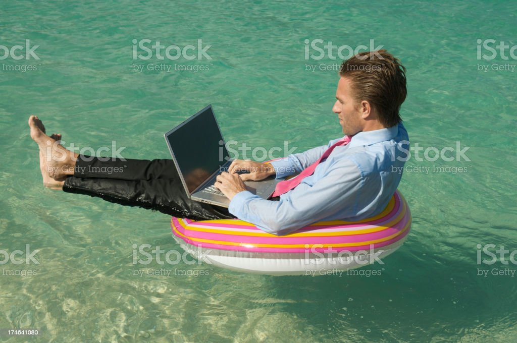 Relaxed Businessman Keeping Afloat on Tropical Sea with Laptop royalty-free stock photo