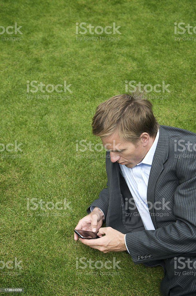 Relaxed Businessman Lying on Grass Texting royalty-free stock photo