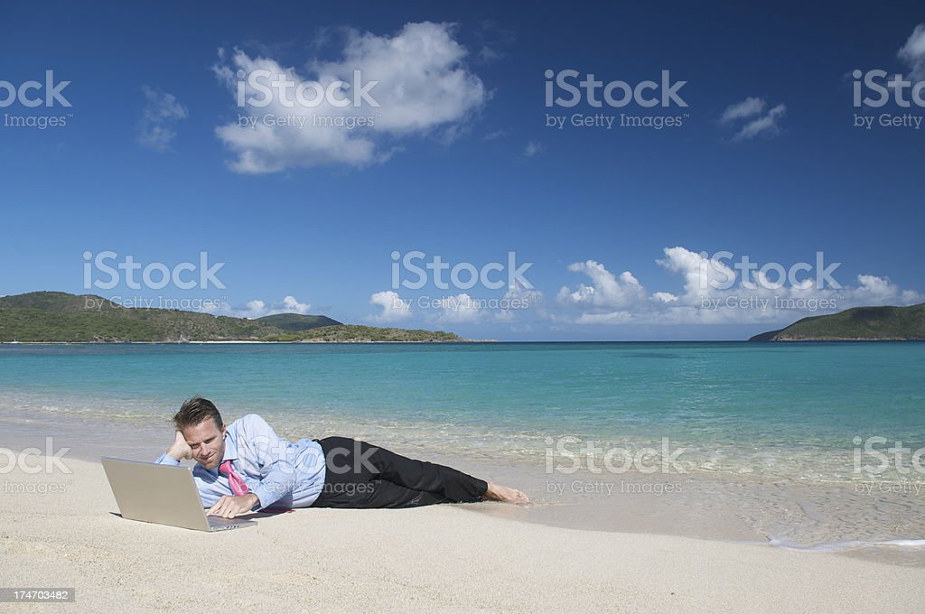 Relaxed Businessman Lying on Tropical Beach Working Laptop Computer royalty-free stock photo