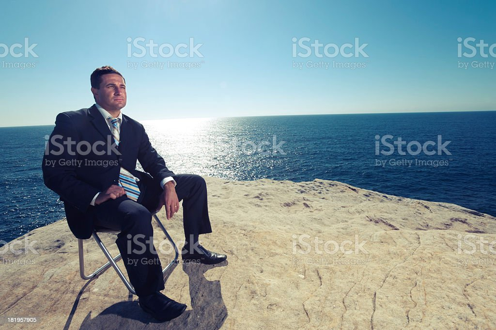 Relaxed businessman sitting by the ocean royalty-free stock photo