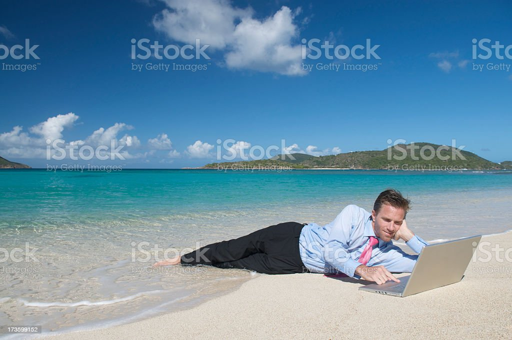 Relaxed Businessman Surfing the Web on Tropical Beach stock photo