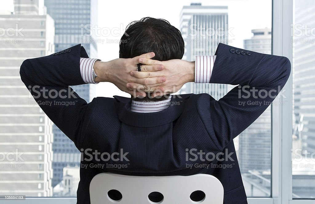 Relaxed businessman turns to window with hands behind head stock photo