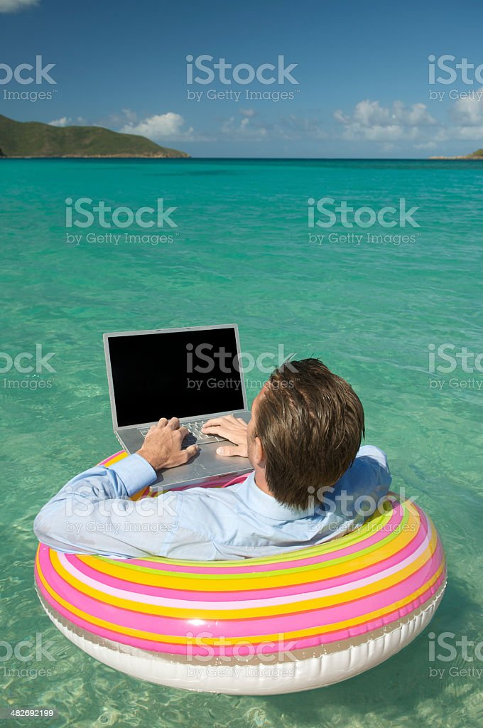 Relaxed Businessman Typing on Laptop Floating in Tropical Bay royalty-free stock photo