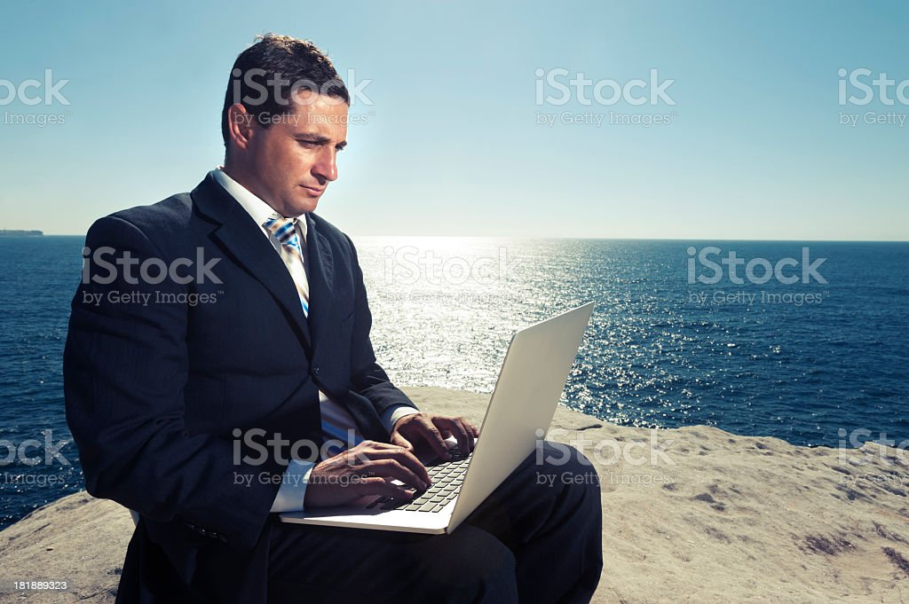Relaxed businessman working on laptop outdoors royalty-free stock photo