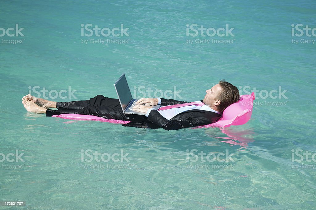 Relaxed Businessman Working Typing on Lilo Floating in Tropical Water royalty-free stock photo