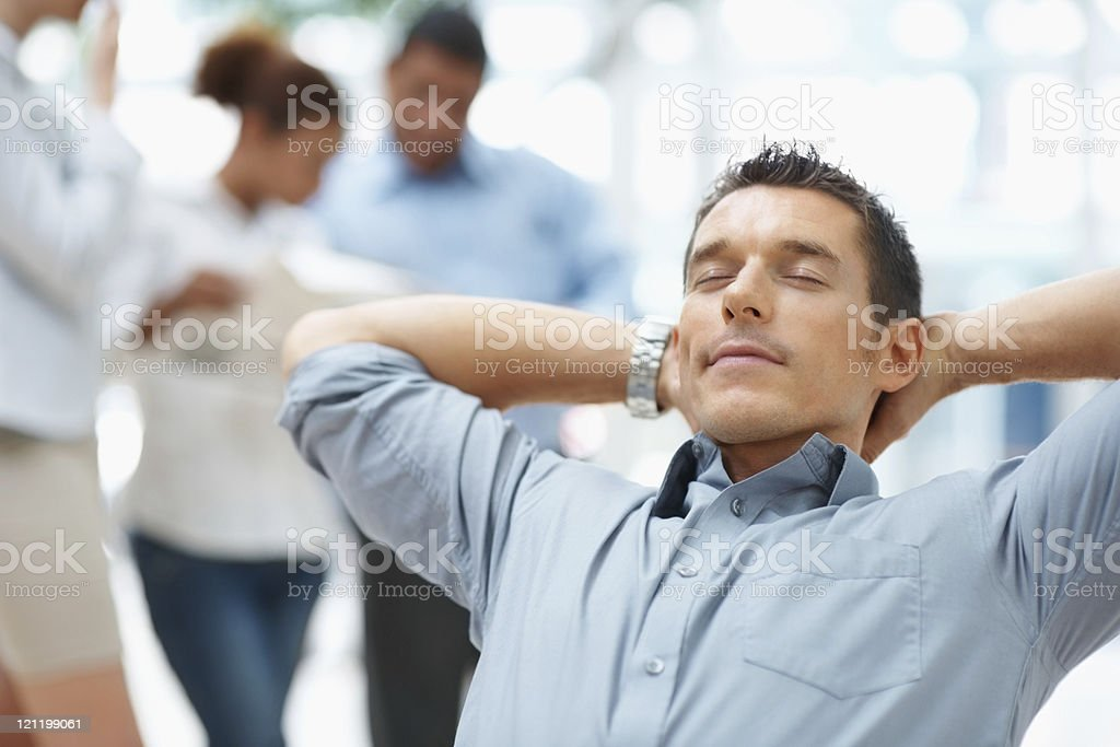 Relaxed confident business man with colleagues at the back stock photo
