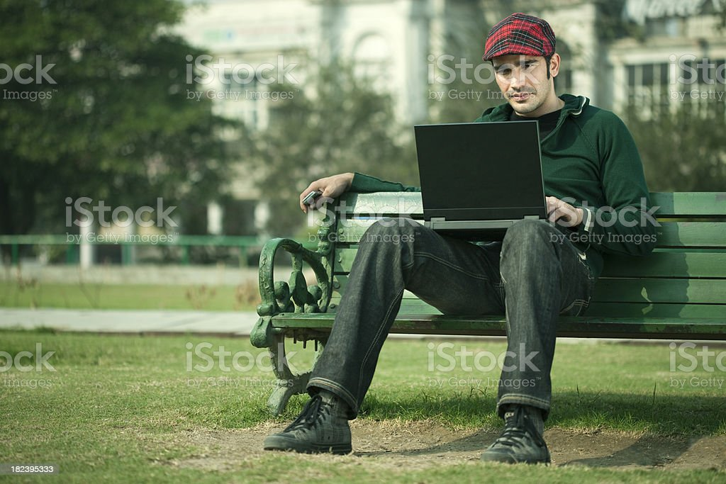 Relaxed, confident young man reading on a laptop screen royalty-free stock photo