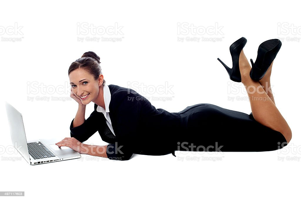 Relaxed corporate woman working on laptop stock photo