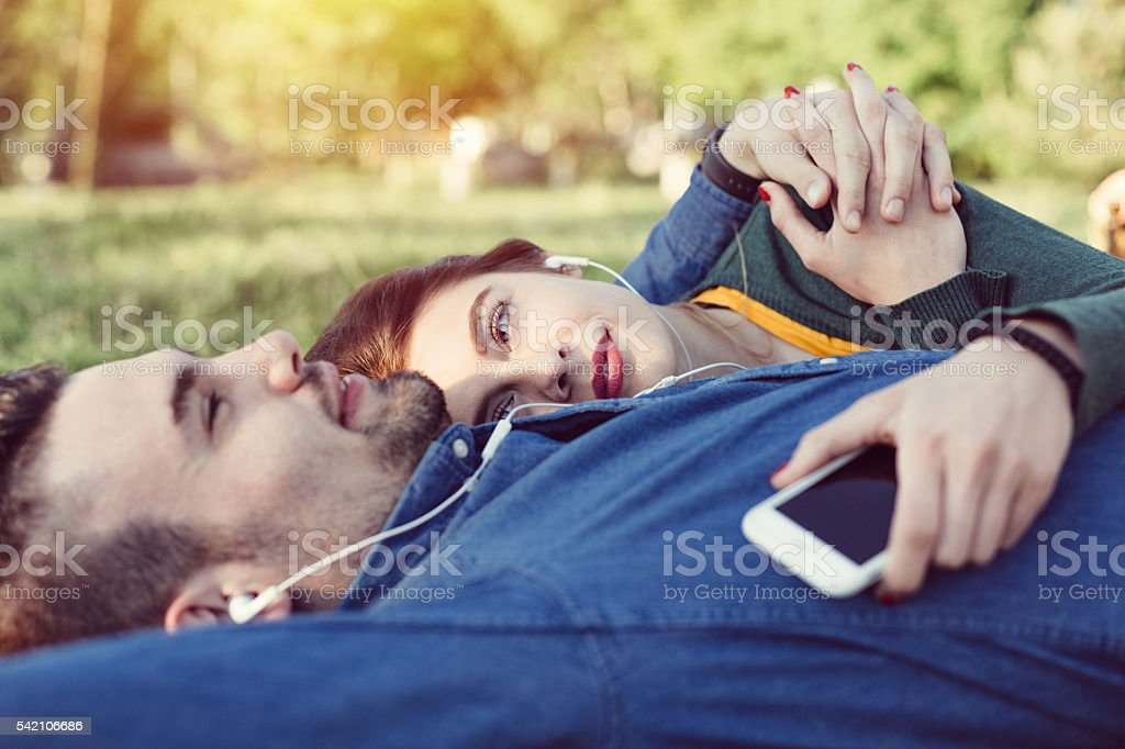 Relaxed couple enjoying the music in the park stock photo